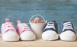 Baby shoes and colorful candy in bucket. Baby shoes and colorful candy in white pail royalty free stock image