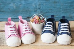Baby shoes and colorful candy in bucket. Baby shoes and colorful candy in white pail royalty free stock photo