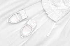Baby shoes on dress Stock Photos