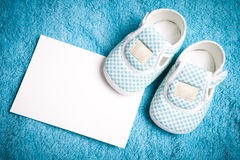 Baby shoes and empty postcard. On blue background Stock Photography