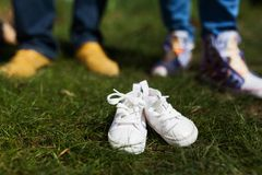 Baby shoes in front of future parents. Married couple is waiting for their future baby Stock Image