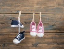 Baby shoes hanging on the clothesline. Baby shoes hanging on the colorful clothesline over wooden background Royalty Free Stock Photos