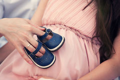 Baby shoes on her belly. Baby shoes on the belly of a pregnant woman Royalty Free Stock Photography