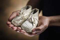 Baby Shoes. Man holding old and worn leather baby shoes in his hands Stock Photos