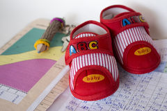 Baby shoes on the  mother's diary. Baby shoes on the pregnant mother's diary Royalty Free Stock Photo