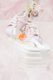 Baby shoes and orange pacifier on cotton diapers Stock Photos