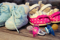 Baby shoes and pacifiers pink and blue on the old wooden background. Toned image Royalty Free Stock Image