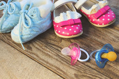 Baby shoes and pacifiers pink and blue Stock Image