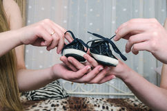 Baby shoes on parental hand. Baby's bootees Stock Image