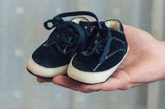 Baby shoes on parental hand. Baby's bootees Royalty Free Stock Photo