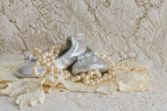Baby Shoes and Pearls on Lace Handkerchief Stock Images
