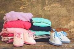 Baby shoes, pink and blue clothing on the old wooden background. Stock Image