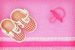 Baby shoes and pink pacifier Stock Image