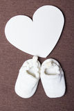 Baby shoes and plastic heart over brown Stock Images