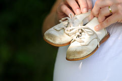 Baby shoes on pregnant belly. Old scuffed baby shoes held against pregnant belly Stock Photos