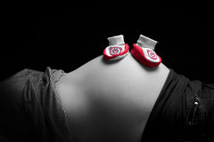 Baby shoes on pregnant belly Stock Image