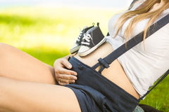 Baby shoes on pregnant mother stomach lying on grass at park Royalty Free Stock Photo
