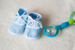 Baby shoes and rattle on light background Stock Photos