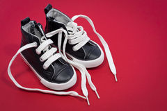 Baby shoes on red background Stock Photos