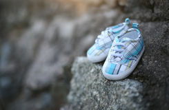 Baby shoes on the rock. Blue baby shoes on the rock royalty free stock photography