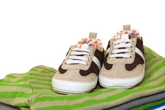 Baby shoes and T-shirts isolated on white Stock Photo