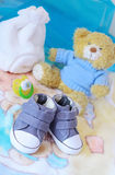 Baby shoes and teddy bear in blue. Blue baby background - baby shoes, cap, dummy and teddy bear and pregnant identity card royalty free stock images