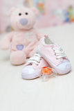 Baby shoes and teddy bear toy on a wooden floor Stock Photography