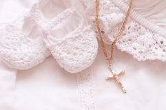 Baby shoes and white dress with golden cross Royalty Free Stock Photos