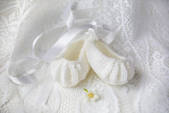 Baby Shoes. White hand knitted baby ballet shoes on white lace background royalty free stock photography