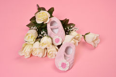 Baby shoes and white roses Royalty Free Stock Image