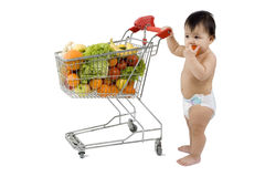 Baby with shopping cart. Baby pushes a shopping cart with fruits and vegetables before a white background Royalty Free Stock Photography