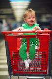 Baby in shopping cart Stock Image