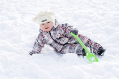 Baby with shovel lying in snow in winter Stock Photos