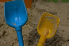 Baby shovels for sand close up. Children`s shovels for sand close up on a background of sand stock photography