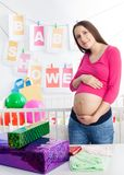 Baby shower. Pregnant woman at her baby shower event stroking her belly Royalty Free Stock Photos