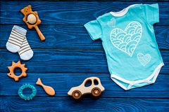Baby shower concept. Baby`s clothes and toys on blue wooden background top view. Clothes for boy copy space. Baby shower concept. Baby`s clothes and toys on blue royalty free stock photography