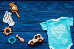 Baby shower concept. Baby`s clothes and toys on blue wooden background top view. Clothes for boy copy space. Baby shower concept. Baby`s clothes and toys on blue stock photos