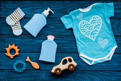 Baby shower concept. Baby`s clothes and toys on blue wooden background top view. Clothes for boy. Baby shower concept. Baby`s clothes and toys on blue wooden stock images