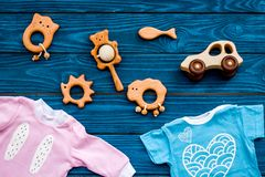 Baby shower concept. Baby`s clothes and toys on blue wooden background top view.  royalty free stock photos