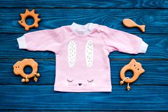 Baby shower concept. Baby`s clothes and toys on blue wooden background top view.  royalty free stock photography