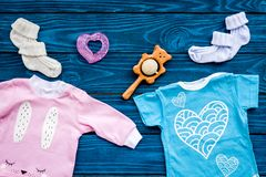Baby shower concept. Baby`s clothes and toys on blue wooden background top view.  royalty free stock images