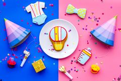 Baby shower. Cookies in shape of accesssories for child, party hats and confetti on pink and blue background top view.  stock photo