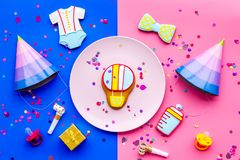 Baby shower. Cookies in shape of accesssories for child, party hats and confetti on pink and blue background top view.  stock images