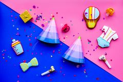Baby shower. Cookies in shape of accesssories for child, party hats and confetti on pink and blue background top view.  stock photography