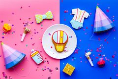 Baby shower. Cookies in shape of accesssories for child, party hats and confetti on pink and blue background top view.  royalty free stock photography