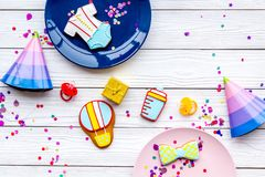Baby shower. Cookies in shape of accesssories for child, party hats and confetti on white wooden background top view.  royalty free stock photo