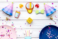 Baby shower. Cookies in shape of accesssories for child, party hats and confetti on white wooden background top view.  stock photos