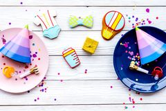 Baby shower. Cookies in shape of accesssories for child, party hats and confetti on white wooden background top view.  stock image