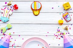 Baby shower. Cookies in shape of accesssories for child, party hats and confetti on white wooden background top view.  royalty free stock photography