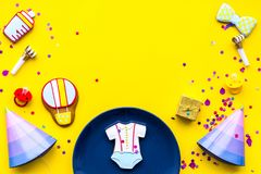 Baby shower. Cookies in shape of accesssories for child, party hats and confetti on yellow background top view copy. Baby shower. Cookies in shape of stock image